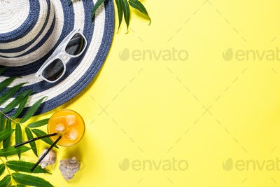 Summer travel vacation concept.  Striped hat and sunglasses on yellow.