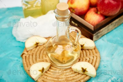 Glass Bottle of apple organic vinegar on blue background.
