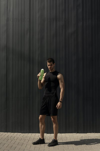 Portrait muscular man taking a break to hydrate his body after training.