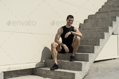 Smiling sportsman sitting at the base of ascending stairs
