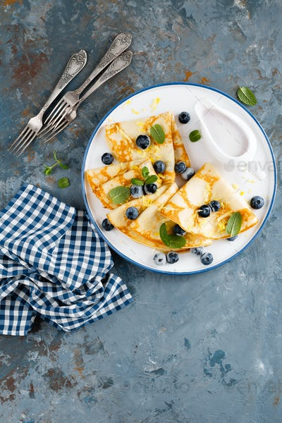 Sweet pancakes wrapped with fresh berries, crepes with blueberry, top view