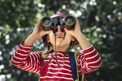 Little girl using binoculars in the forest