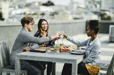 Friends toasting at a rooftop dinner party