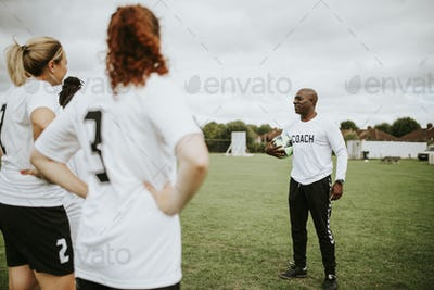 Female football players listening to the coach