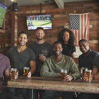 Group Of Friends Meeting And Drinking Beer In Sports Bar Together At Camera