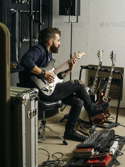 Playing his electric guitar in the recording studio