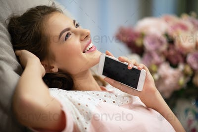Happy young woman  with smart phone dreaming at home.