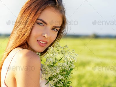 Happy and smiling beautiful woman  outdoor with flowers in hands