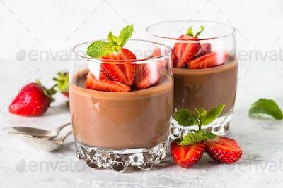 Chocolate panna cotta sweet dessert with strawberries in glass.