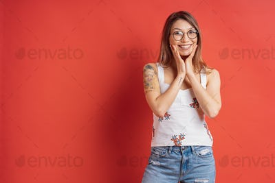 People emotions - portrait of surprised positive girl over red background