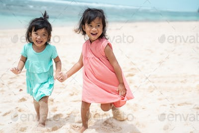 two little girl running with hold hand enjoy playing together