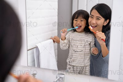 mom and kid brushing their teeth together