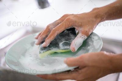 female hand gesture cleaning plate using sponge