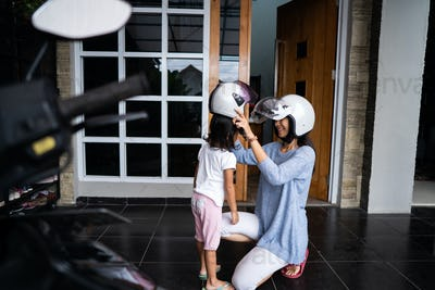 mom helped her daughter to put on helmet