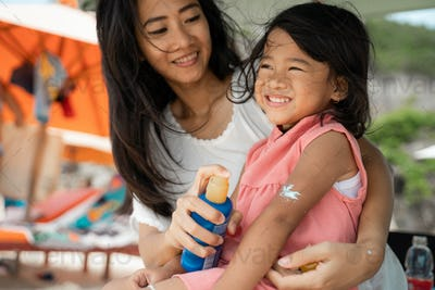 a daughter feels amused when mother give a sunblock to his arm