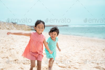 two little girl walking together on white sand beach
