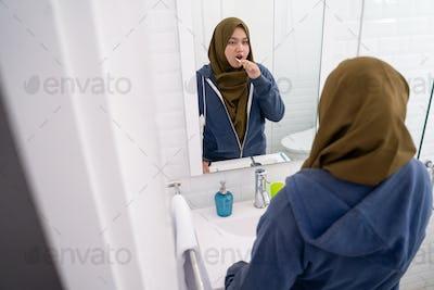 woman wearing hijab brush her teeth