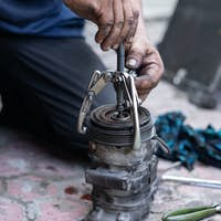 a mechanic with bearing tracker tool will remove a pulley