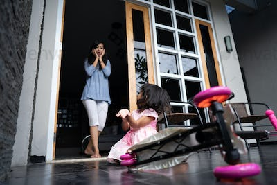 shocked mom looking at her daughter fell from scooter