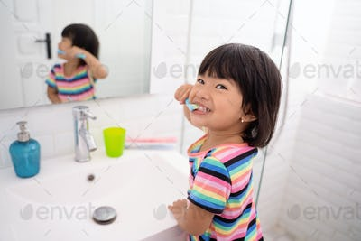 asian little girl brushes her teeth and shows her teeth when brushing her teeth
