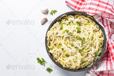 Pasta carbonara with bacon and cream sauce on white.