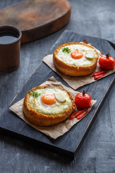 Bread with cheese and yolk for breakfast on black cutting board