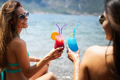 Beautiful fit girls in summer day having fun and cocktails on beach