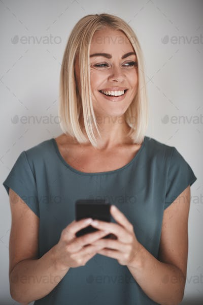 Female entrepreneur smiling while reading texts against a gray background