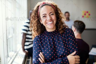 Smiling female designer standing in an modern office