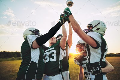 Cheering American football team raising a championship trophy in victory