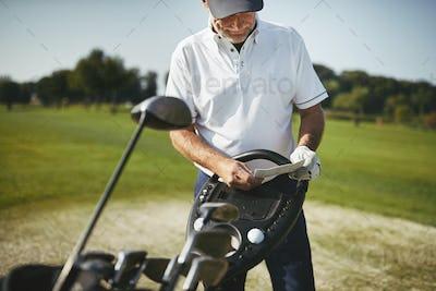 Senior man reading his scorecard during a golf game