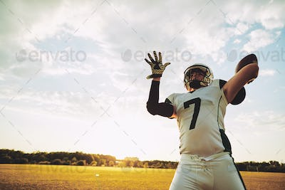 Football quarterback about to throw a pass during team practice