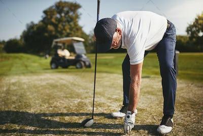 Senior man preparing to tee off on a golf course