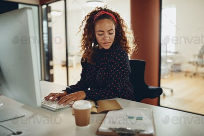 Young businesswoman working at her desk in an empty office