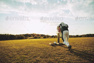 American football player doing sled tackle drills during practice
