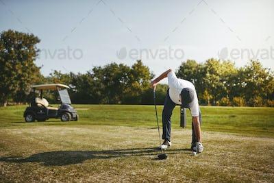 Senior man putting his ball on a golf tee