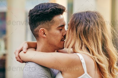 Romantic young couple kissing together on a city street