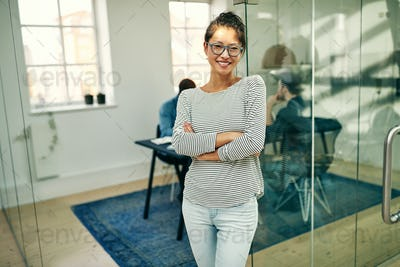 Smiling young Asian businesswoman standing by an office boardroom