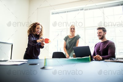 Laughing coworkers playing table tennis together in an office