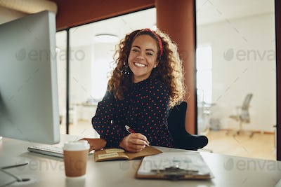 Smiling businesswoman writing down notes while working at her desk