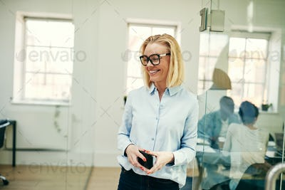 Laughing businesswoman standing with her cellphone in a modern office