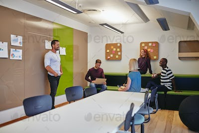 Smiling group of designers talking together in a modern office