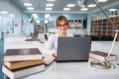 Female student studying at the laptop in library