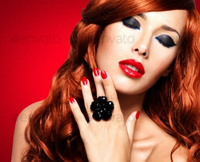 Beautiful fashionable woman with red nails and red hairs