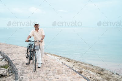asian old man riding his bike at the beach
