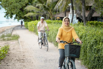happy senior muslim couple exercising riding bicycle together