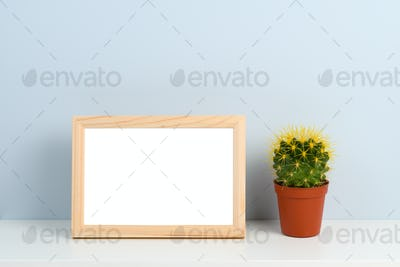 Wooden photo frame and cactus on shelf