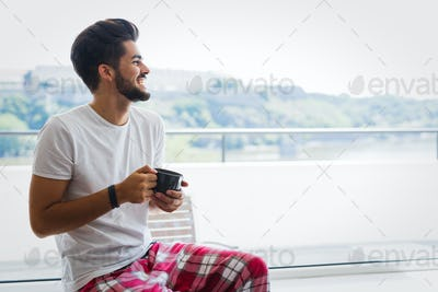 Young man drinking coffee at home in morning