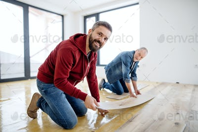 A mature man with his senior father laying vinyl flooring, a new home concept.