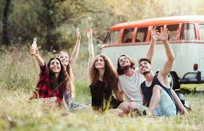 A group of young friends with drinks sitting on grass on a roadtrip through countryside.